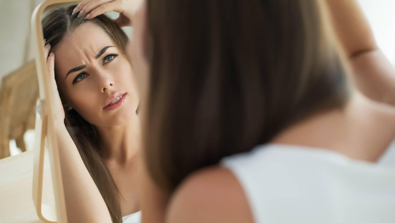 Mulher passando por problemas de queda de cabelo feminino