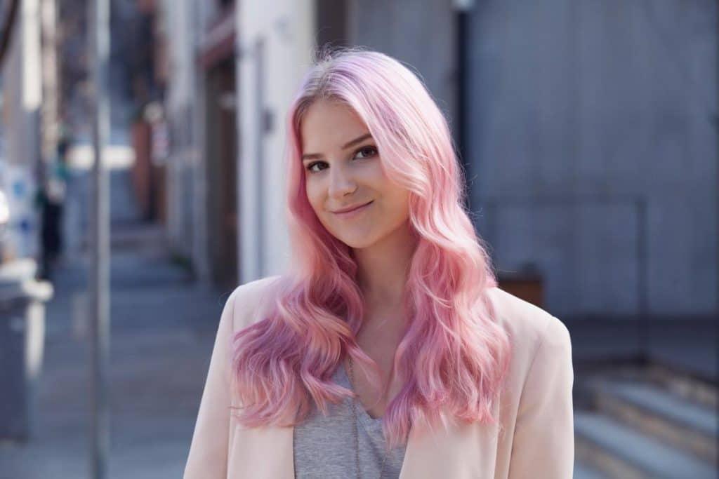 Mulher com cabelo rosa sorrindo devido a ter realizado tratamento antiqueda para cabelo colorido