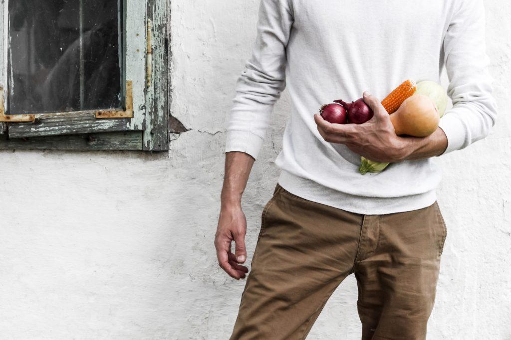 Homem segurando alimentos que ajudam a evitar a calvície