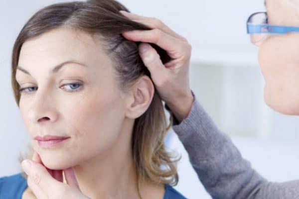 Profissional realizando exame para definir implante de cabelo preço