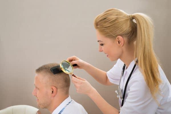 Mulher examinando paciente para saber implante capilar resultados
