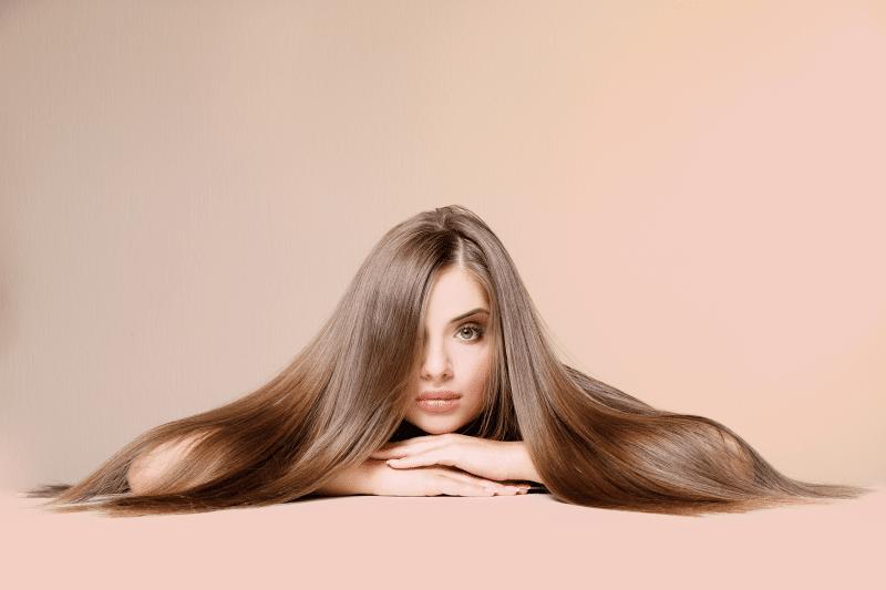Mulher deitada sobre fios de seus próprios cabelos
